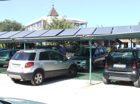 Solar car port: this one in Italy is used to head water for adjacent hotel, but we will increasingly see PV panels used to charge EVs